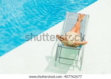 Top view of a girl in the swimming pool on a sun lounger - stock photo