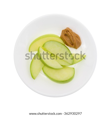 Top view of a group of green apple slices on a dish with a small amount of peanut butter for dipping isolated on a white background. - stock photo