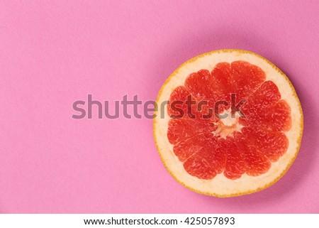 Top view of a half of fresh citrus grapefruit. Ripe juicy fruit. Juicy poster with grapefruit. Red grapefruit on a pink background. Grapefruit cut in half on pink paper texture. - stock photo