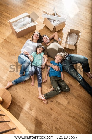 Top view of a happy family in casual clothes laying on the wooden floor of their new flat with cardboard boxes around them They are looking at camera The smiling parents are holding their two children - stock photo
