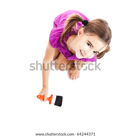 Top view of a happy girl sitting on floor holding a paint-brush - stock photo