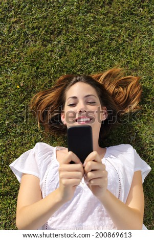 Top view of a happy woman with white dress lying on the grass texting on a smart phone                 - stock photo