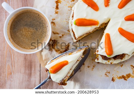 Top view of a homemade carrot cake with mascarpone cream cheese icing and handmade mini marzipan carrot decorations with a cup of hot black coffee - stock photo