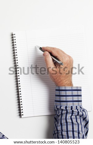 Top view of a human hand writing on book over white background. - stock photo