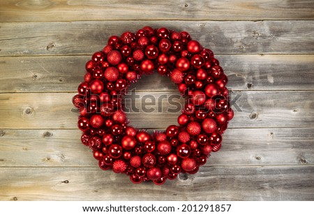 Top view of a large Christmas Wreath made with red ornaments on rustic wood - stock photo