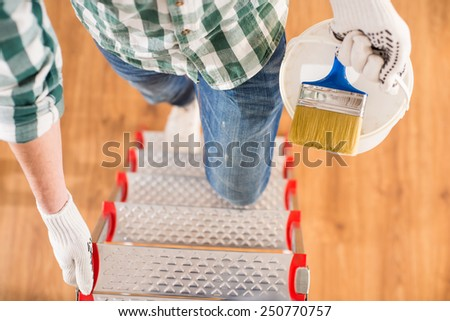 Top view of a man is standing on a ladder with a paint brush to paint walls. - stock photo