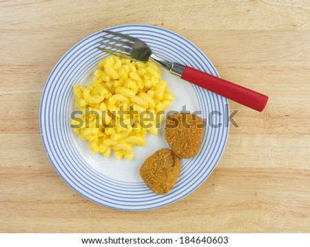 Top view of a meal of macaroni and cheese with two chicken nuggets on a blue striped plate with a red handled fork on a wood tabletop. - stock photo