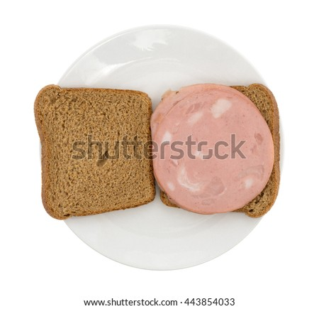 Top view of a mortadella sandwich in whole wheat bread open faced upon a plate isolated on a white background. - stock photo