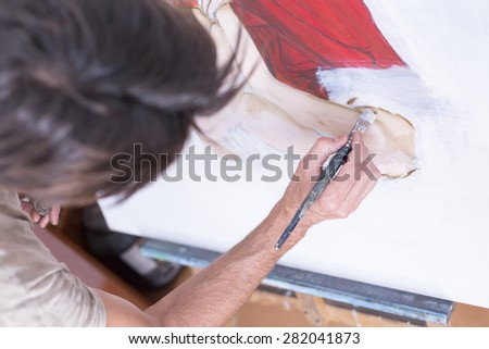 top view of a painter painting on canvas at his painting studio - focus on the paintbrush - stock photo