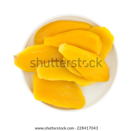 Top view of a plate of canned mango slices atop a white background. - stock photo