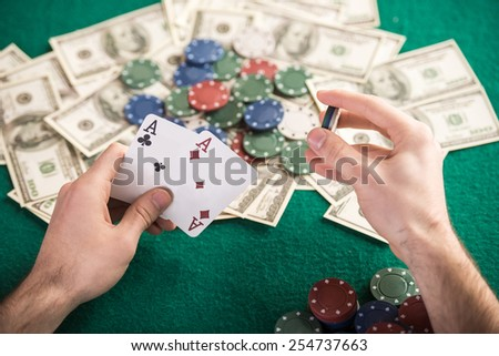 Top view of a poker table during a game. Chips, money and cards on the table. - stock photo