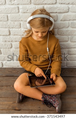 Top view of a pretty little blonde girl listening to music and using tablet while sitting cross-legged against white brick wall - stock photo