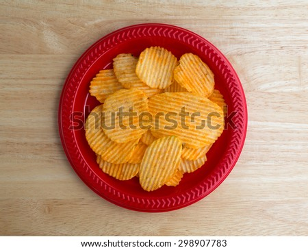 Top view of a red plastic plate with a serving of cheddar cheese flavored potato chips on a wood table top illuminated with natural light. - stock photo