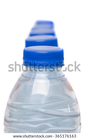 Top view of a row of plastic water bottles isolated on a white background. - stock photo