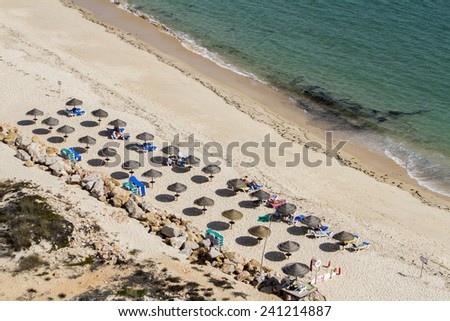 Top view of a section of straw umbrellas on a beach with turquoise water.  - stock photo