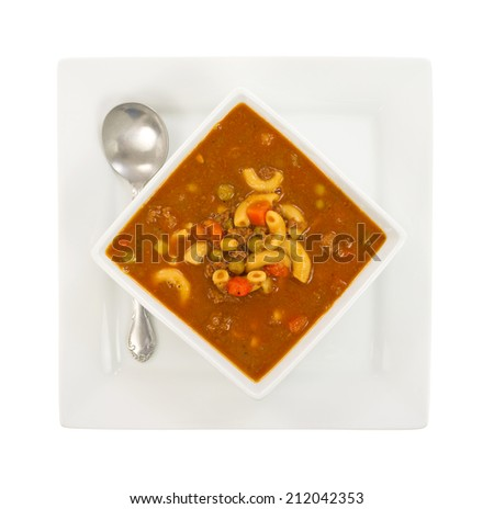 Top view of a serving of hamburger soup in a square bowl with plate beneath and a spoon to the side on a white background. - stock photo