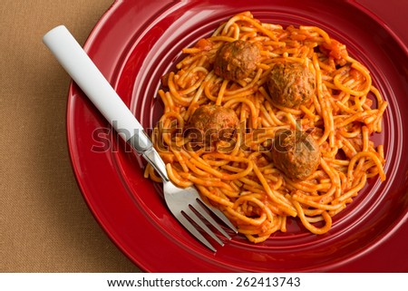 Top view of a spaghetti and meatball TV dinner on a red plate with a fork on a tan table cloth. - stock photo