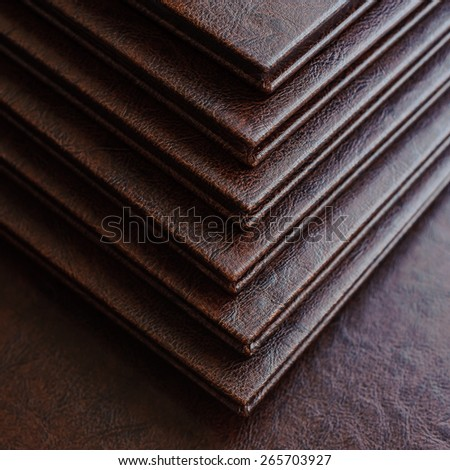 top view of a stack of books in a brown leather hardcover, closeup - stock photo