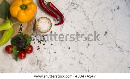 Top view of a yellow bell pepper, red chilli peppers, green peppers, cherry tomatoes, basil leaves and crushed salt on a white marble background with copy space. - stock photo