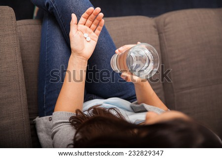 Top view of a young woman holding a glass of water and about to take a couple of aspirins - stock photo