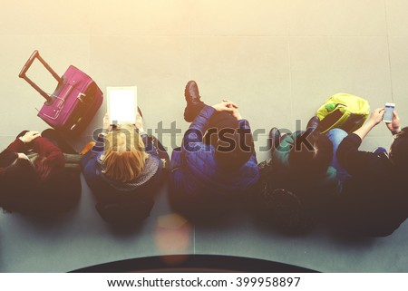 Top view of a young women are chatting on their cell telephone and touch pad, while are waiting plane in airport hall. Female is holding digital tablet with blank copy space screen for your content  - stock photo