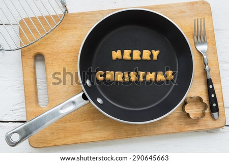 Top view of alphabet text collage made of cookies biscuits. Word MERRY CHRISTMAS putting in frying pan. Other utensils: fork, cookie cutter and cutting board putting on wooden table, vintage style. - stock photo