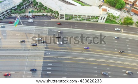 Top view of an asphalt elevated highway in Houston, Texas, US. Many passenger cars and trucks are commuting in freeway at late afternoon, warm light.Great for urban transportation publication.Panorama - stock photo