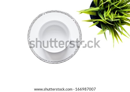 Top view of an empty white cup and saucer against a white background with a green potted plant.  - stock photo