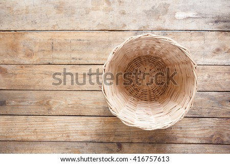 Top view of an empty wicker basket on old wooden floor. - stock photo