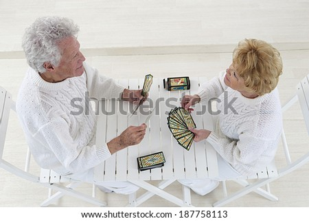 top view of an happy old couple playing together with cards at home  - stock photo