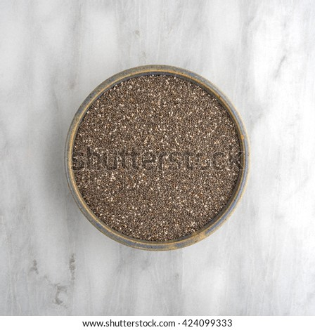 Top view of an old stoneware bowl filled with organic chia seeds on a marble cutting board. - stock photo