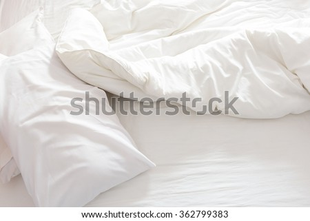 Top view of an unmade bed with crumpled bed sheet, a blanket and pillows after waking up in the morning. - stock photo