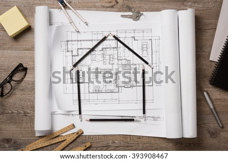 Top view of architectural blueprints, rolls and drawing instruments on the worktable. Shape of house with black pencils on a project house. Architectural drawings with house keys, new home concept. - stock photo