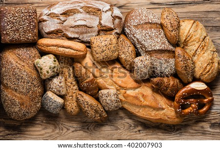 Top view of assortment of different kind of cereal bakery: bread, pasties, buns, pretzel and croissant on old wooden background. - stock photo