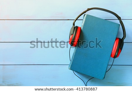 top view of audio book concept, blue cover book and headphones over wooden table - stock photo