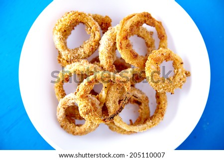 Top view of baked onion rings snacks in white plate on blue background. Healthy fast food recipe. - stock photo