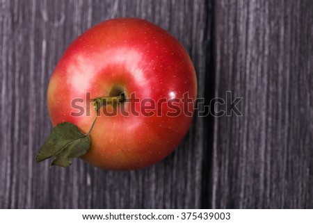 Top view of beautiful ripe round red yellow apple with green leaf on shank on grey wooden timber background, horizontal photo - stock photo