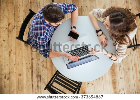 Top view of beautiful young couple talking, using laptop and holding blank screen cell phone at the round table in cafe - stock photo
