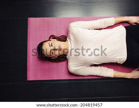 Top view of beautiful young woman lying on yoga mat after workout. Fit female relaxing on floor at home. - stock photo