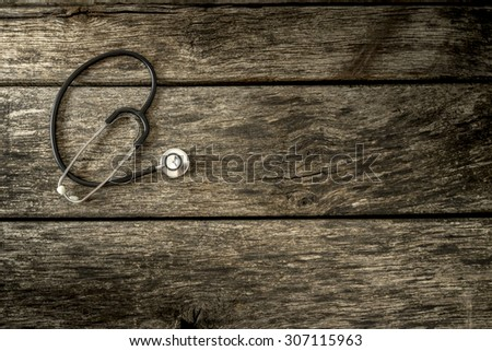 Top view of black medical stethoscope lying on aged textured wooden planks with additional copyspace to the right. - stock photo