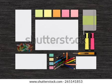 Top view of blank colorful template on black desk for corporate branding identity presentation or portfolio. Mockup consists of envelopes, notebook, pencils, business card, letterhead, markers. - stock photo