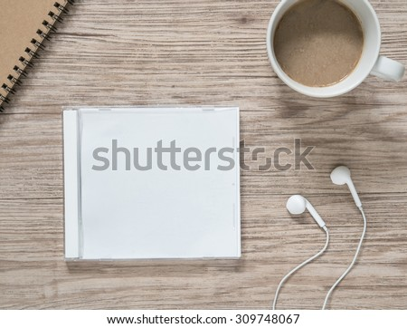 Top view of blank compact disc (CD) with cover , earphones, notebook and coffee on wooden background  - stock photo
