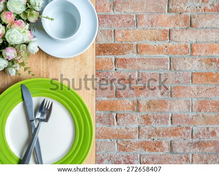Top view of blank plate on wooden top/ rustic brick copy space background - stock photo
