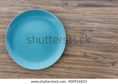 Top view of blue empty plate on wooden background with copy space - stock photo