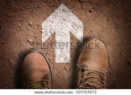 Top View of Boot on the trail with Direction Arrow - stock photo