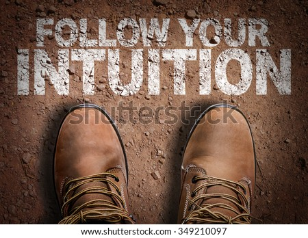 Top View of Boot on the trail with the text: Follow Your Intuition - stock photo