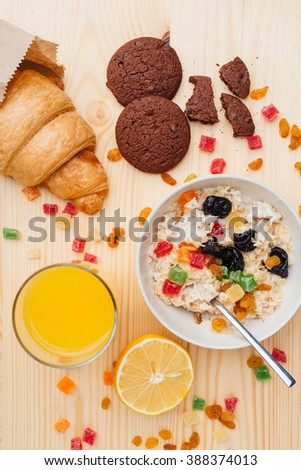 Top view of bowl with oat flackes, croissant, cookies and fresh juice in a mess on the table - stock photo