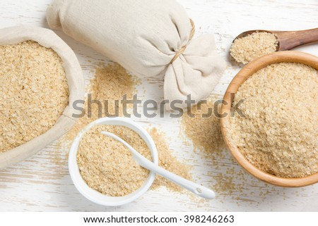 Top view of bowls full of amaranth seeds on white wooden surface; healthy eating concept - stock photo