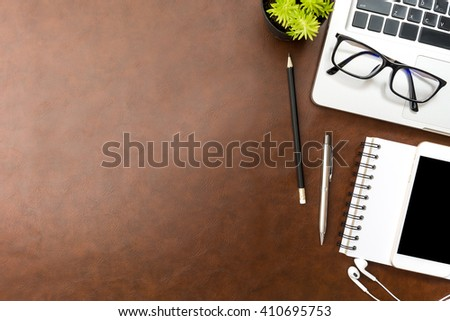 Top view of brown leather desk with laptop and office supplies. Top view with copy space. - stock photo