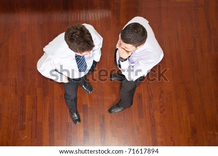 Top view of business man telling his collegue a secret and holding hands to month and the other man listening him - stock photo